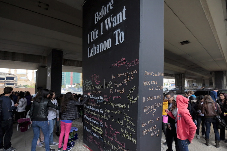 Lebanese students write on walls during an event to mark the 40th anniversary of Lebanon's civil war (1975-1990) along a street of Beirut's former green-line