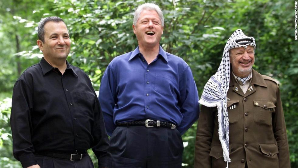 En julio del año 2000, el entonces primer ministro israelí Ehud Barak, el expresidente Bill Clinton, y Yasir Arafat, reunieron a sus respectivas delegaciones en Camp David para intentar alcanzar una solución al conflicto palestino-israelí. En la fotografía, tomada el 21 de julio, los líderes posan para la prensa. Un periodista le pide a Clinton declaraciones acerca del estado de las negociaciones, y Clinton responde que las partes acordaron no emitir comentarios. El periodista pregunta entonces: ¿es eso lo único que han acordado hasta ahora?. El presidente se ríe. Crédito por la imagen: Stephen Jaffe / AFP.